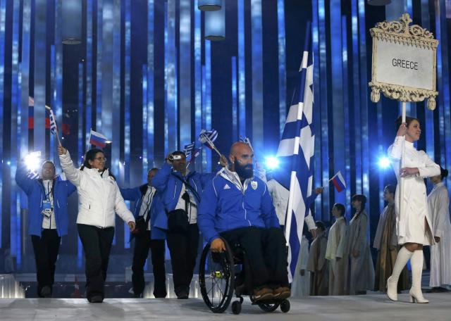 Greece's flag-bearer Efthymios Karalas (C), leads his country's contingent during the opening ceremony of the 2014 Paralympic Winter Games in Sochi, March 7, 2014. REUTERS/Alexander Demianchuk (RUSSIA - Tags: OLYMPICS SPORT)