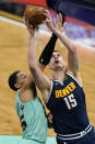 Denver Nuggets center Nikola Jokic, right, is fouled by Charlotte Hornets forward P.J. Washington during the first half of an NBA basketball game on Tuesday, May 11, 2021, in Charlotte, N.C. (AP Photo/Chris Carlson)