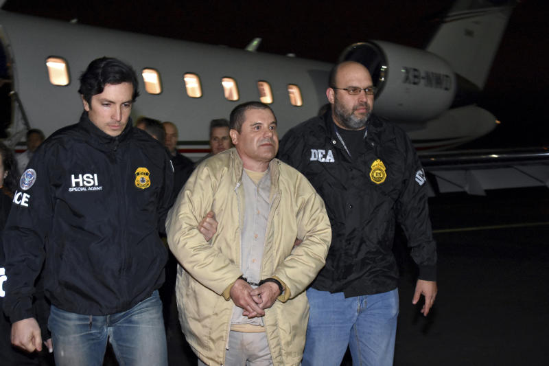 "Joaquin ""El Chapo"" Guzman is escorted from a plane to a waiting caravan of SUVs in New York's Long Island on Jan. 19, 2017. (Associated Press)"