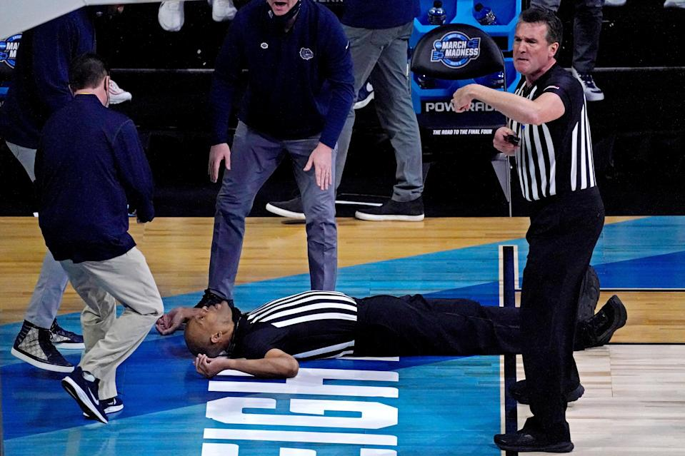 Medical personnel attend to referee Bert Smith after he collapsed on the court during the first half of the Elite Eight game between Gonzaga and Southern California.