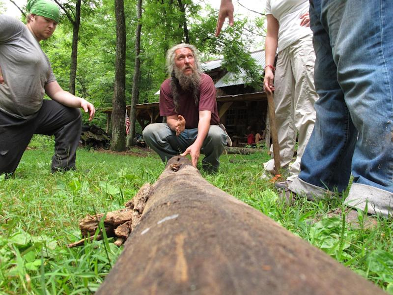 """Eustace Conway, center, shows campers how to split a log at his Turtle Island Preserve in Triplett, N.C., on Thursday, June 27, 2013. When Conway bought his first 107 acres in 1987, his vision for Turtle Island was as """"a tiny bowl in the earth, intact and natural, surrounded by pavement and highways."""" People peering inside from nearby ridges would see """"a pristine and green example of what the whole world once looked like."""" (AP Photo/Allen Breed)"""