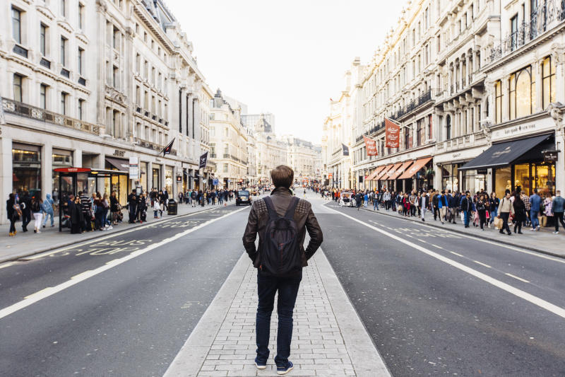 Rear view of a man with backpack exploring street of London, England, UK