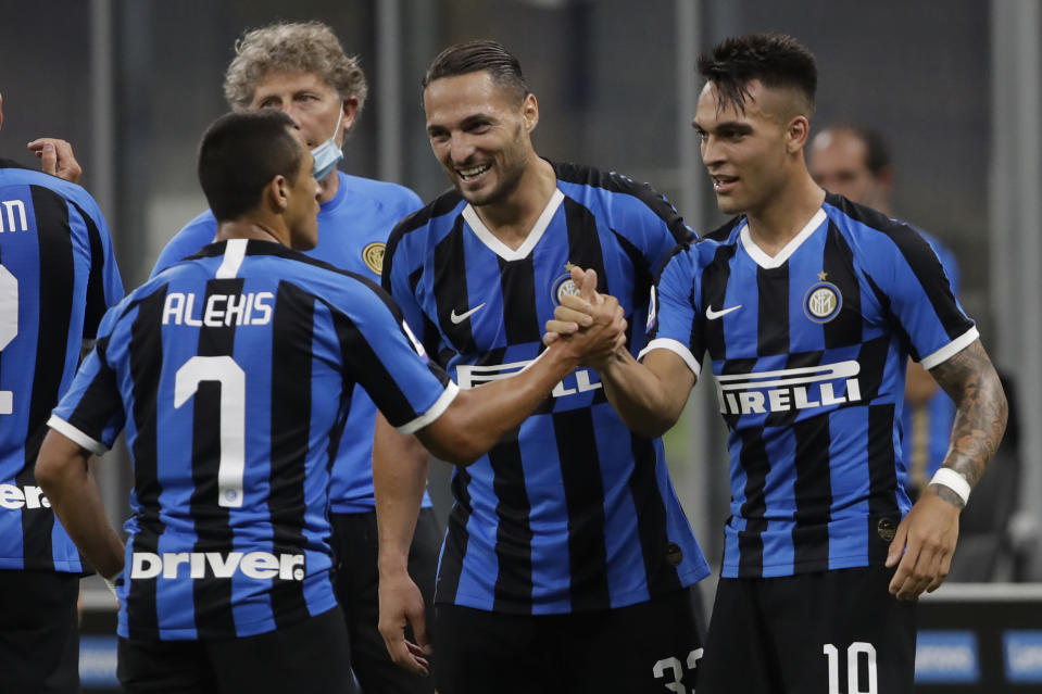 Inter Milan's Lautaro Martinez, right, celebrates after scoring his side's third goal during a Serie A soccer match between Inter Milan and Torino, at the San Siro stadium in Milan, Italy, Monday, July 13, 2020. (AP Photo/Luca Bruno