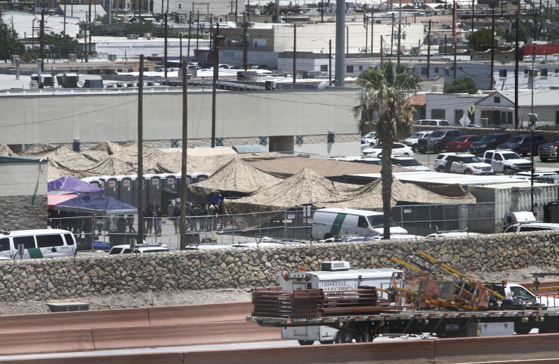 In this June 12, 2019 ,photo, migrants are seen within a fenced-off area inside a temporary outdoor encampment where they're waiting to be processed in El Paso, Texas. The Trump administration is facing growing complaints from migrants about severe overcrowding, meager food and other hardships at border holding centers like this one. (AP Photo/Cedar Attanasio)