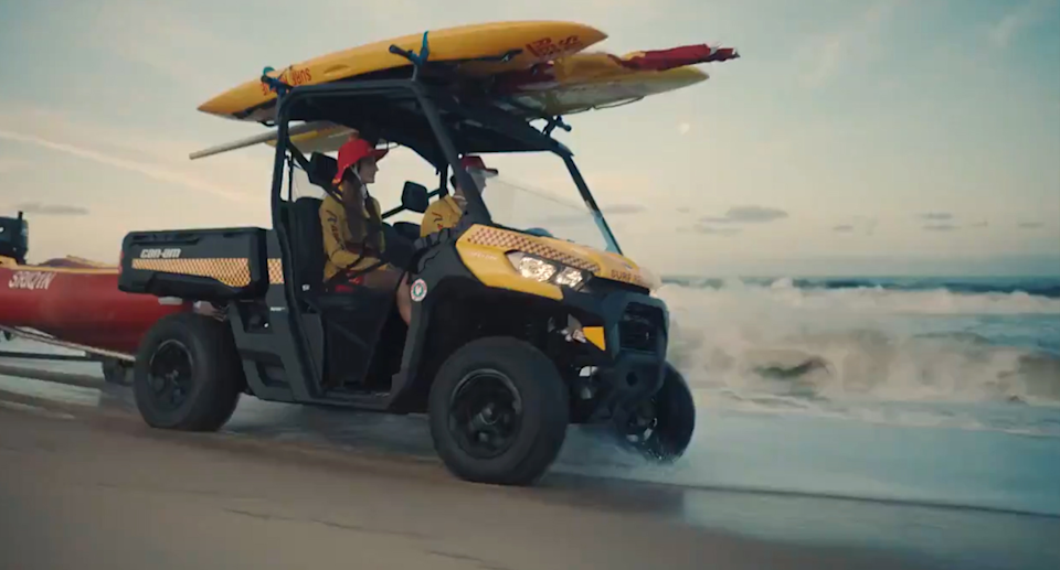 Surf Life Savers can be seen driving along the beach as the commercial begins. Source: Surf Life Saving Australia