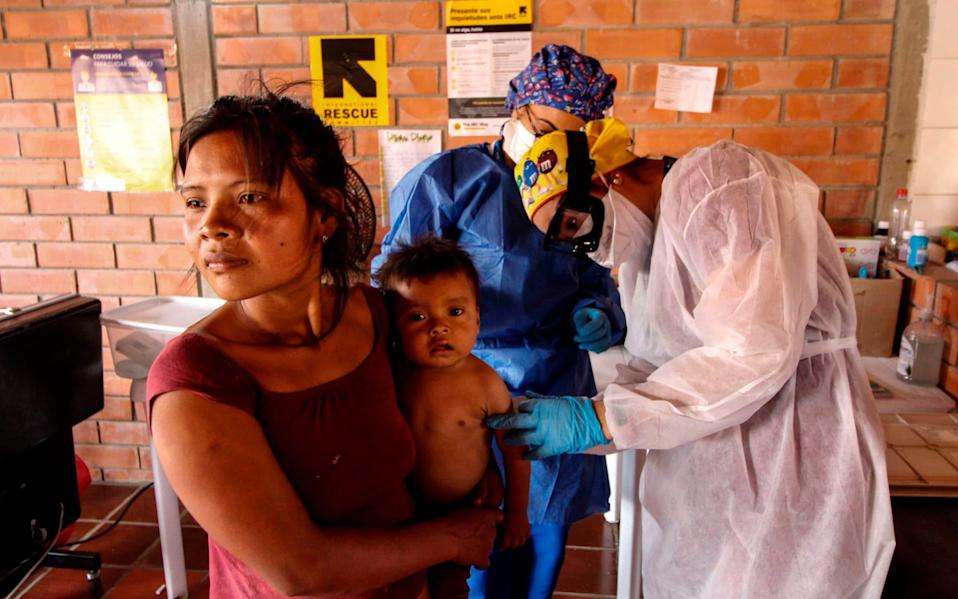 Health care workers check members of an Indigenous community - SCHNEYDER MENDOZA/AFP via Getty Images