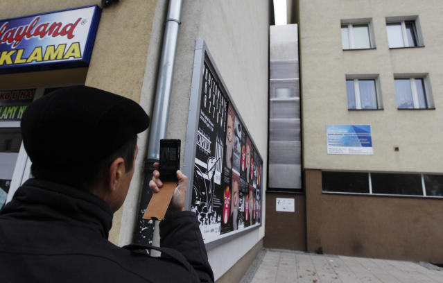 A man takes a picture of the one of the world's narrowest buildings, built as an artistic installation wedged between two existing buildings, in Warsaw October 23, 2012. A building just 92 cm (36 inches) wide as its narrowest point was opened in Warsaw on October 20 as an artistic installation that will be a home from home for Israeli writer Edgar Keret. Keret, who told news channel TVN24 he would live there when he visits Warsaw twice a year, said he conceived the project as a kind of memorial to his parents' family who died in the World War Two Holocaust. Picture taken October 23, 2012. To match story POLAND-NARROW/ REUTERS/Kacper Pempel (POLAND - Tags: SOCIETY) - RTR39M9N