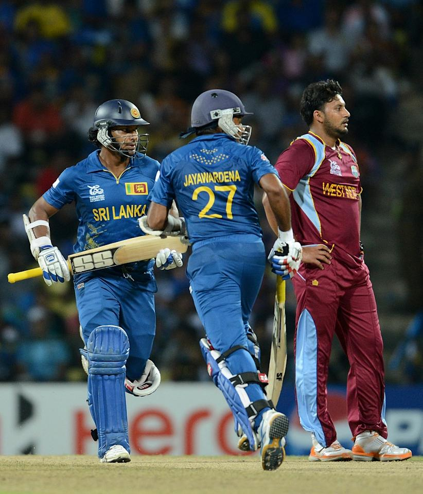 West Indies bowler Ravi Rampaul (R) watches as Sri Lankan batsmen Mahela Jayawardene (C) and Kumar Sangakkara (L) run between the wickets during the ICC Twenty20 Cricket World Cup's  (L) Super Eight match between Sri Lanka and West Indies at The Pallekele International Cricket Stadium in Pallekele on September 29, 2012. AFP PHOTO/ Prakash SINGH