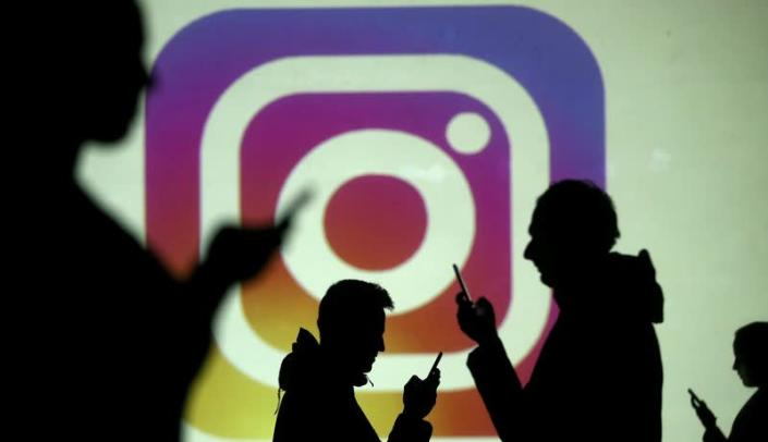 FILE PHOTO: FILE PHOTO: Silhouettes of mobile users are seen next to a screen projection of Instagram logo in this picture illustration
