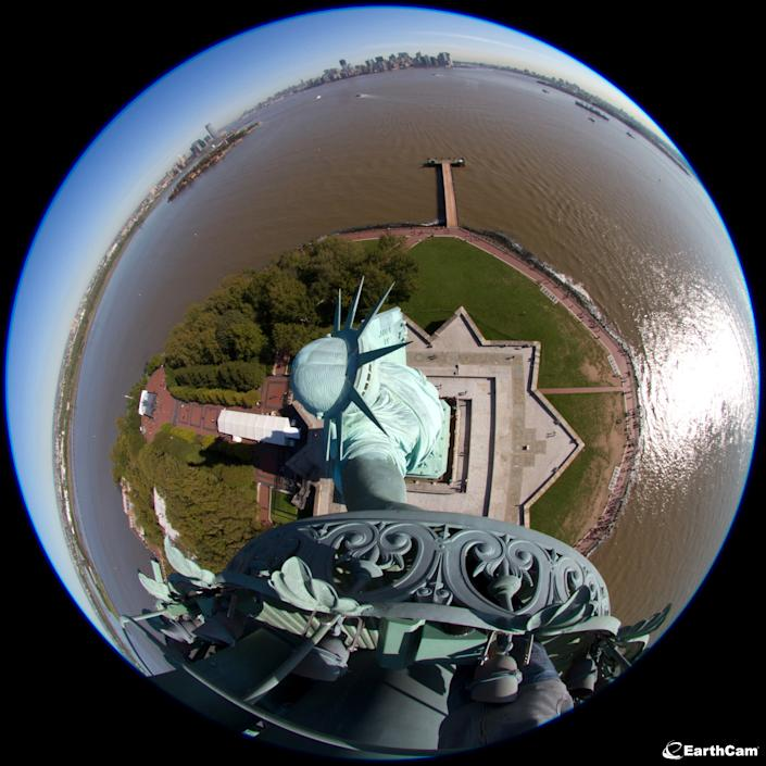 This undated photo provided by EarthCam, shows the Statue of Liberty in New York Harbor, in New York, through a fisheye lens mounted in its torch. Five torch cams will be switched on Friday, Oct. 28, 2011, during a ceremony to commemorate the statue's dedication. The five cameras, which will be on 24 hours, 7 days a week, were donated to the National Park Service by Earthcam Inc., a New Jersey-based company that manages a network of webcams around the world. (AP Photo/EarthCam, James Nicoll)