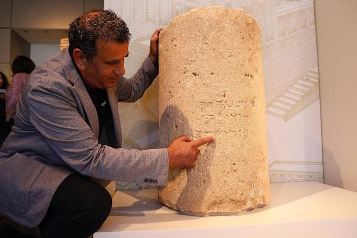 Israel Antiquities Authority archaeologist Yuval Baruch points at a unique stone inscription dating to the period of the second Jewish temple (first century AD) (AFP Photo/GALI TIBBON)