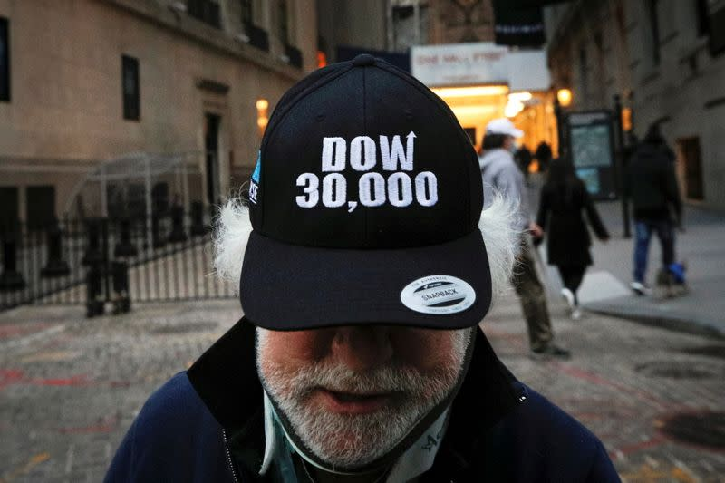 Trader Peter Tuchman wears a DOW 30,000 hat as he greets friends outside the New York Stock Exchange (NYSE) in New York