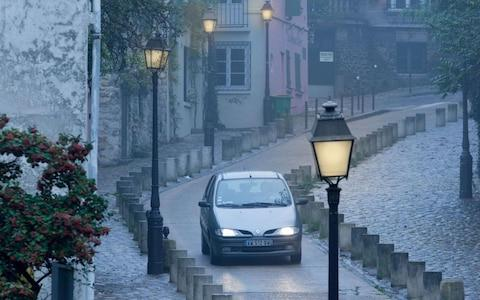 Car driving on a narrow road with headlights turned on in gloomy weather - Credit: Alamy