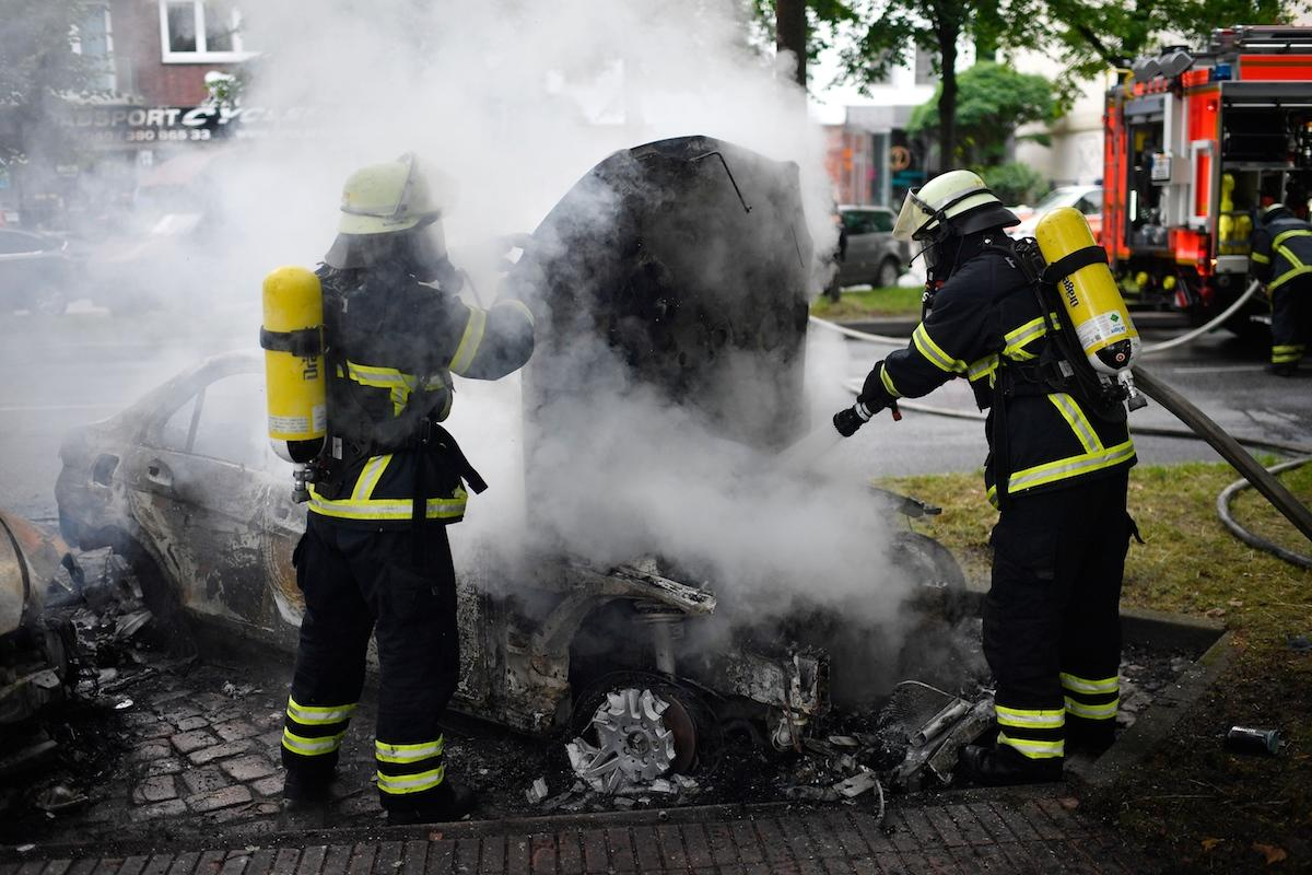 Fire crews extinguish a burning car in the street during the 'Welcome to Hell' anti-G20 protest march. (Alexander Koerner/Getty Images)