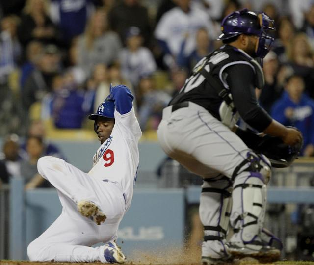 Los Angeles Dodgers' Dee Gordon (9) scores on a single to left field by Dodgers' Yasiel Puig, as the throw is cut off en route to Colorado Rockies catcher Wilin Rosario, right, in the third inning of a baseball game on Friday, April 25, 2014, in Los Angeles. (AP Photo/Alex Gallardo)