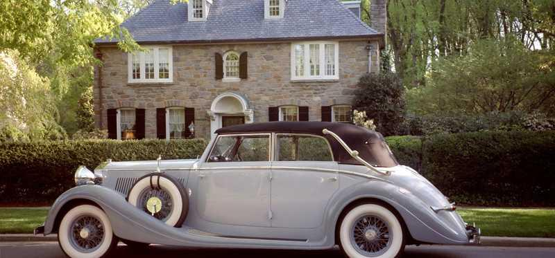 A nice, antique car in front of a large home.