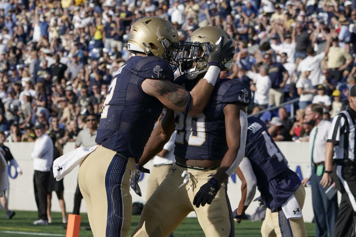 Navy's Daniel Taylor, right, is congratulated by Tyger Goslin after he recovered a blocked punt by Navy on a kick by UCF for a touchdown during the first half of an NCAA college football game, Saturday, Oct. 2, 2021, in Annapolis, Md. (AP Photo/Julio Cortez)