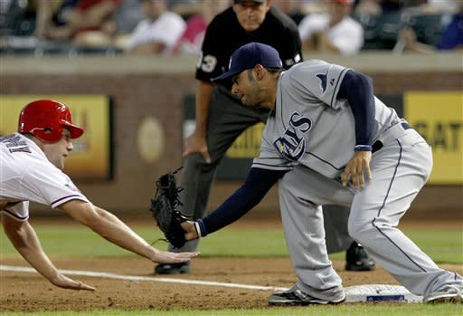 Texas Rangers' David Murphy attempts to get back to first on a pick-off attempt as Tampa Bay Rays' Carlos Pena reaches down to apply the tag in the third inning of a baseball game, Tuesday, Aug. 28, 2012, in Arlington, Texas. First base umpire Mike Winters, rear, watches the play. (AP Photo/Tony Gutierrez)