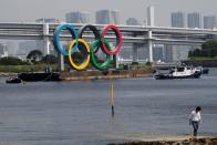 Boats tow the giant Olympic rings, which are being temporarily removed for maintenance, at the waterfront area at Odaiba Marine Park in Tokyo