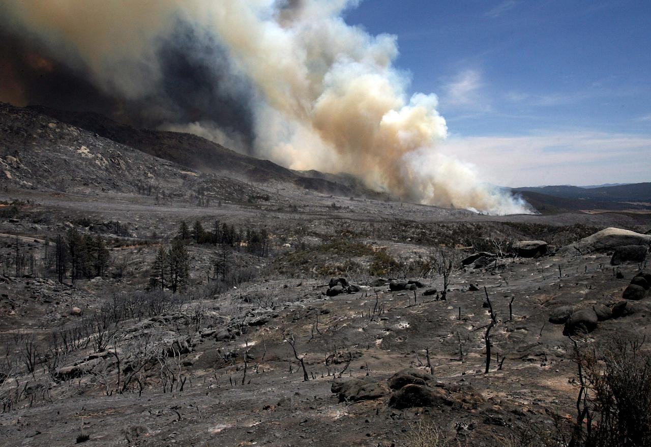 Looking at the blackened landscape from the Mountain Fire near Lake Hemet on Tuesday July 16, 2013. The 14,200 acre forest fire near Idyllwild Calif., has caused Idyllwild and adjacent communities east of Highway 243 to issued mandatory evacuations for hundreds of homes Wednesday. (AP Photo/The Press-Enterprise, Frank Bellino)