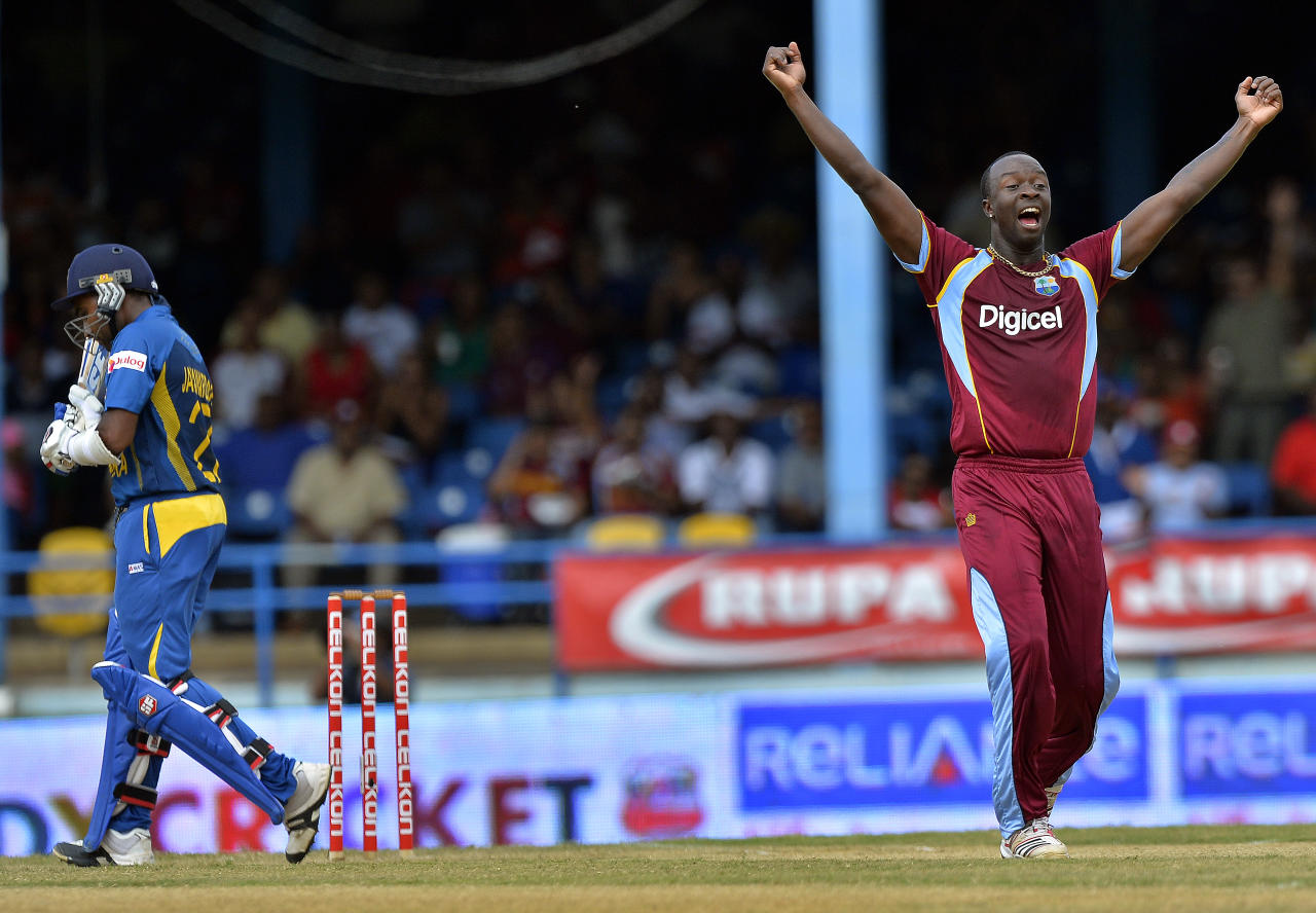 West Indies bowler Kemar Roach (R) celebrates dismissing Sri Lankan batsman Mahela Jayawardene (L) during the fifth match of the Tri-Nation series between Sri Lanka and West Indies at the Queen's Park Oval in Port of Spain on July 7, 2013. West Indies won the toss and elected to field. AFP PHOTO/Jewel Samad