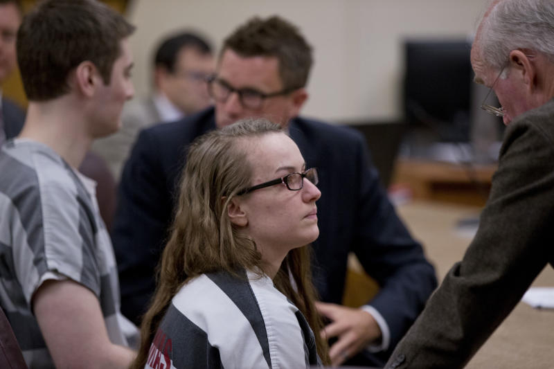 Sarah Mitchell, center, and Travis Lee Mitchell, left, the parents of a twin girl who struggled to breath and died a few hours later after a home birth, appear in court in Oregon City, Ore., Monday, July 9, 2018. The couple, members of the Followers of Christ Church, that shuns traditional medicine in favor of prayer and anointing the sick with oils, have pleaded guilty to negligent homicide in the death of their premature daughter. (Beth Nakamura/The Oregonian via AP)