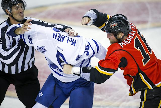 Toronto Maple Leafs' Frazer McLaren, left, fights with Calgary Flames' Brian McGrattan during the first period of an NHL hockey game in Calgary, Alberta, Wednesday, Oct. 30, 2013. (AP Photo/The Canadian Press, Jeff McIntosh)