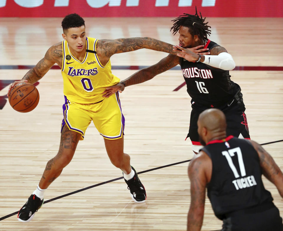 Los Angeles Lakers forward Kyle Kuzma (0) dribbles while defended by Houston Rockets forward Ben McLemore (16) during the first half of an NBA basketball game Thursday, Aug. 6, 2020, in Lake Buena Vista, Fla. (Kim Klement/Pool Photo via AP)
