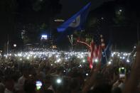 Antigovernment protesters use the flashlights of their mobile phones during a rally in Tirana, Friday, June 21, 2019. The opposition is boycotting the local elections planned for June 30 and has threatened to disrupt them.(AP Photo/Hektor Pustina)