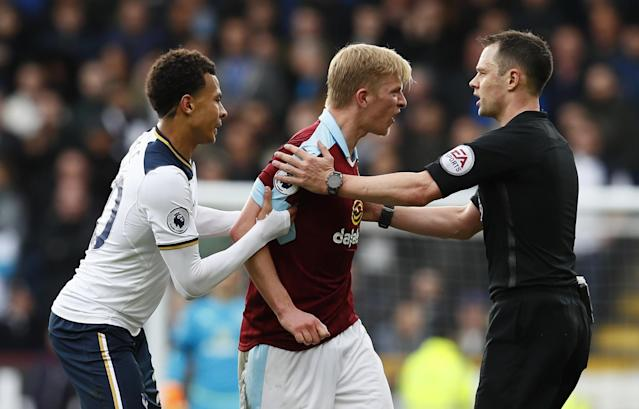 <p>Tottenham's Dele Alli holds on to Burnley's Ben Mee as referee Stuart Attwell speaks to him </p>