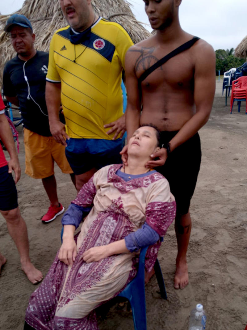 Angelica Gaitan being attended at the beach after being rescued from the water.