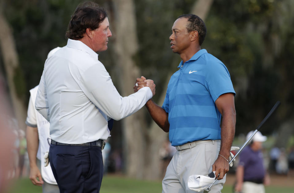"""FILE - In this May 10, 2018, file photo, Phil Mickelson, left, and Tiger Woods shake hands after the first round of the Players Championship golf tournament, in Ponte Vedra Beach, Fla. The winner-take-all match between Tiger Woods and Phil Mickelson is on. WarnerMedia says it has secured the rights for a pay-per-view event it is promoting as """"The Match."""" It will be 18 holes between Woods and Mickelson held Thanksgiving weekend at Shadow Creek in Las Vegas. The winner will receive $9 million. The pay-per-view cost is to be announced later. (AP Photo/Lynne Sladky, File)"""