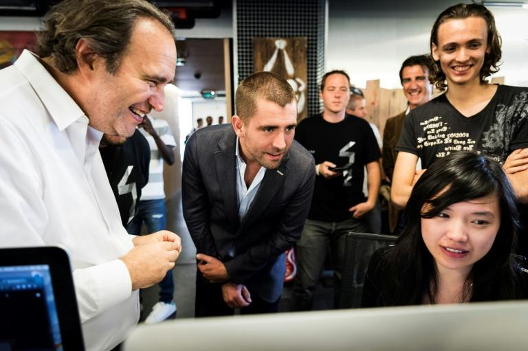 Facebook Chief Product Officer Chris Cox (C) listens to Xavier Niel (L), French businessman and founder of the French telecom and internet company Iliad, and president of the Ecole 42 school (AFP Photo/LIONEL BONAVENTURE)