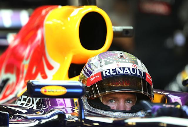 Red Bull driver Sebastian Vettel of Germany waits in his car in his team garage during the third practice session for the Singapore Formula One Grand Prix on the Marina Bay City Circuit in Singapore, Saturday, Sept. 21, 2013. (AP Photo/Wong Maye-E)