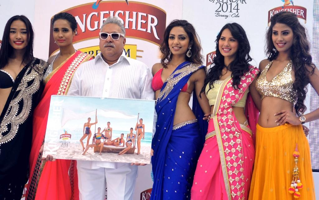 Vijay Mallya (centre in white), a part-owner of the Force India Formula 1 team who used to run a liquor empire, left India on March 2 owing more than $1 billion and is believed to be in Britain (AFP Photo/STR)