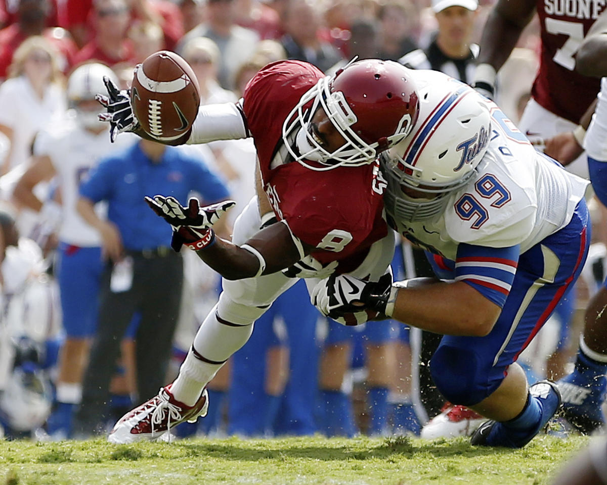 Oklahoma wide receiver Jalen Saunders (8) can't hold onto the pass as he is hit by Tulsa defender Derrick Luetjen (99) in the second quarter of an NCAA college football game in Norman, Okla., Saturday, Sept. 14, 2013. (AP Photo/Sue Ogrocki)