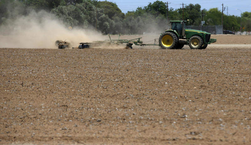 FILE - In this May 23, 2018 file photo a farmer plows a dry and dusty cotton field in Phoenix. Arizona farmers will soon begin planting commercial hemp under a 2018 state law that just took effect once the state issues required licenses. (AP Photo/Ross D. Franklin,File)