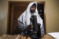 Myon Burrell unpacks a telescope given to him by a supporter so he can watch the stars for the first time in 18 years following his release from prison, Thursday, Dec. 17, 2020, at his home in Minneapolis. Two days earlier, Minnesota's pardon board commuted the sentence of Burrell, 34, a Black man who was sentenced to prison for life as a teen in a high-profile murder case that raised questions about the integrity of the criminal justice system. (AP Photo/John Minchillo)