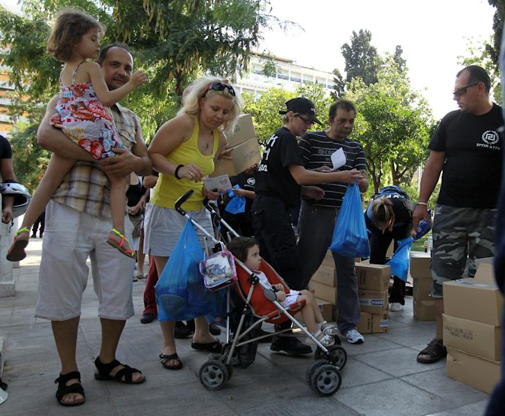 A family receives products from the members of Greece's extreme right Golden Dawn party at Athens' main Syntagma Square, opposite parliament, on Wednesday, Aug. 1, 2012. The volunteers checked ID cards of the public before handing Greek citizens food that included milk cartons, pasta, potatoes and olive oil. Golden Dawn won 18 seats in the 300-seat parliament in June general elections. Senior party members openly support a policy of granting Greek citizenship based on racial identity. The party has stepped up its charity effort as Greece is suffering through a fifth year of recession, with rapidly rising rates of poverty and unemployment. (AP Photo/Thanassis Stavrakis)