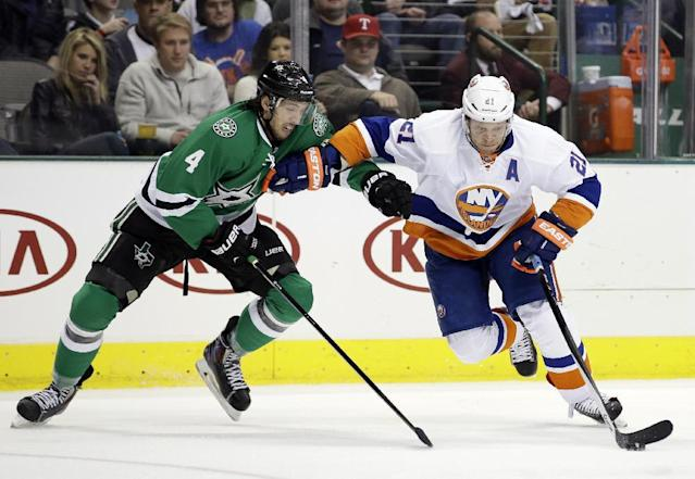 Dallas Stars defenseman Brenden Dillon (4) defends as New York Islanders right wing Kyle Okposo (21) controls the puck in the second period of an NHL hockey game, Sunday, Jan. 12, 2014, in Dallas. (AP Photo/Tony Gutierrez)