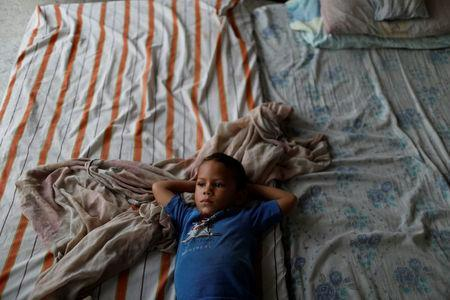 Ismael, son of Cindy Morales, lays down in a mattress at the porch of their home during a blackout in Maracaibo, Venezuela July 25, 2018. Picture taken July 25, 2018. REUTERS/Marco Bello