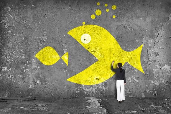 Woman drawing image on a wall of a large yellow fish eating a smaller yellow fish.