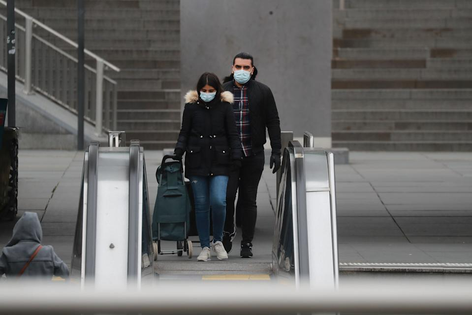 """A couple wearing a protective facemask walks at La Defense, near Paris, on March 16, 2020, while protective measures are taken in France against the spread of the COVID-19. - France has closed down all schools, theatres, cinemas and shops not selling """"non-essential"""" items such as food in an effort to stop the spread of the virus. (Photo by Ludovic Marin / AFP) (Photo by LUDOVIC MARIN/AFP via Getty Images)"""