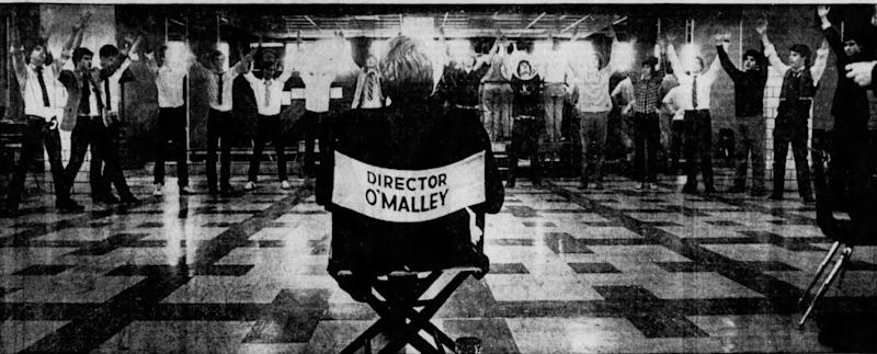Rev. William J. O'Malley directing a student musical, 1983