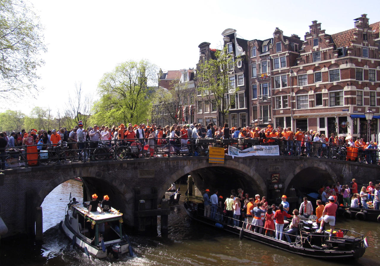 People celebrate Queen's Day at Prinsengracht in Amsterdam, Netherlands, Monday, April 30, 2012, a Dutch national holiday marking the birthday of the Queen's mother. (AP Photo/Margriet Faber)