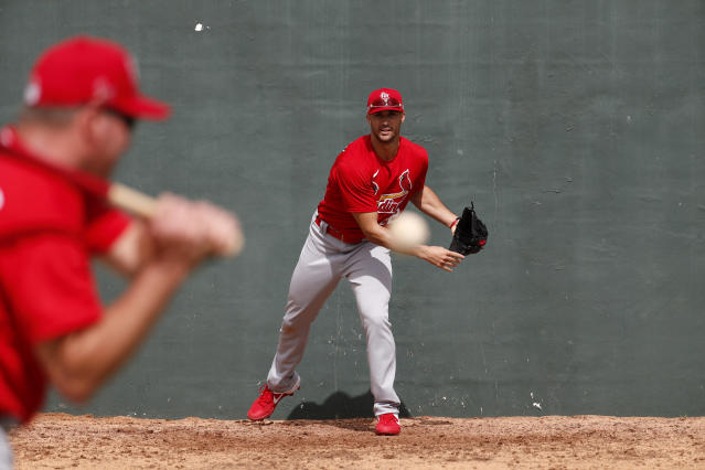 St. Louis Cardinals pitcher Jack Flaherty, right, works on fielding a ball hit back to him by bullpen coach Bryan Eversgerd during spring training baseball practice Sunday, Feb. 16, 2020, in Jupiter, Fla. (AP Photo/Jeff Roberson)