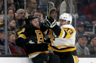 Pittsburgh Penguins left wing Brandon Tanev (13) checks Boston Bruins center Par Lindholm (26) into the boards during the first period of an NHL hockey game, Thursday, Jan. 16, 2020, in Boston. (AP Photo/Mary Schwalm)