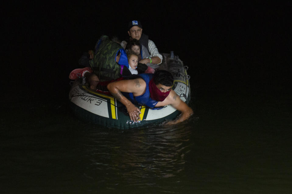 A smuggler takes migrants, mostly from Central American countries, on a small inflatable raft towards U.S. soil in Roma, Texas Tuesday, March 30, 2021. Roma, a town of 10,000 people with historic buildings and boarded-up storefronts in Texas' Rio Grande Valley, is the latest epicenter of illegal crossings, where growing numbers of families and children are entering the United States to seek asylum. (AP Photo/Dario Lopez-Mills)