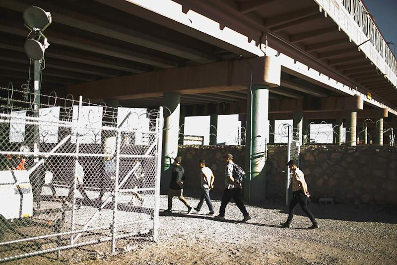 Migrants apprehended by the U.S. Customs and Border patrol are taken to a tent set up underneath the Paso Del Norte Bridge as they await processing in El Paso, Texas, on March 28, 2019. | Jared Moossy for TIME