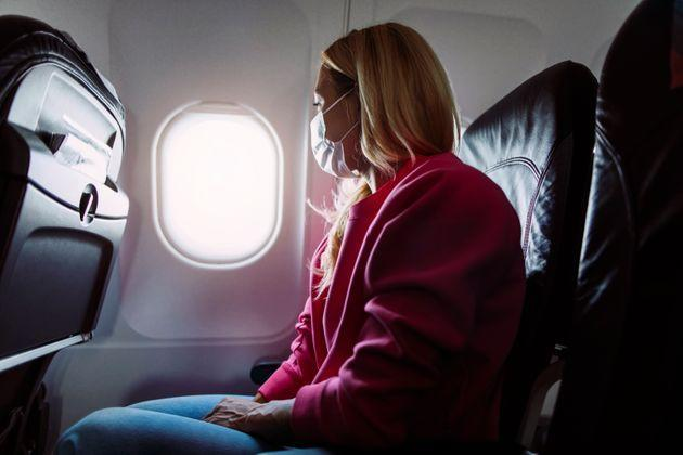 Side shot of a young blond woman sitting in an airplane and looking out of the window (Photo: mihailomilovanovic via Getty Images)